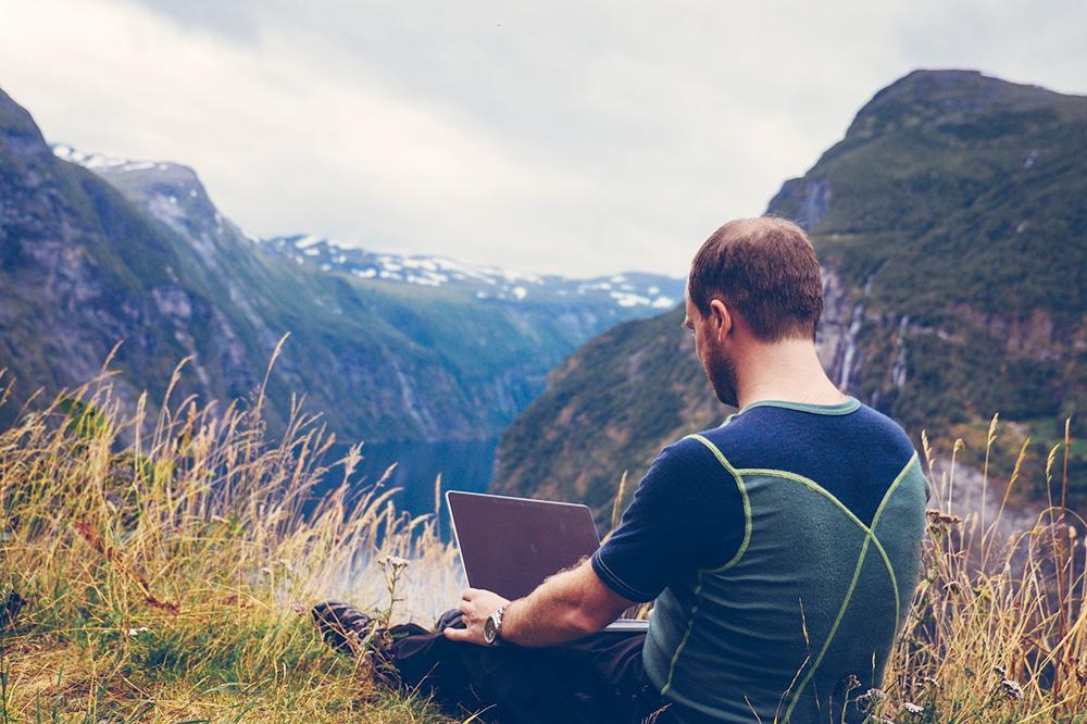 Man på en bergstopp med dator