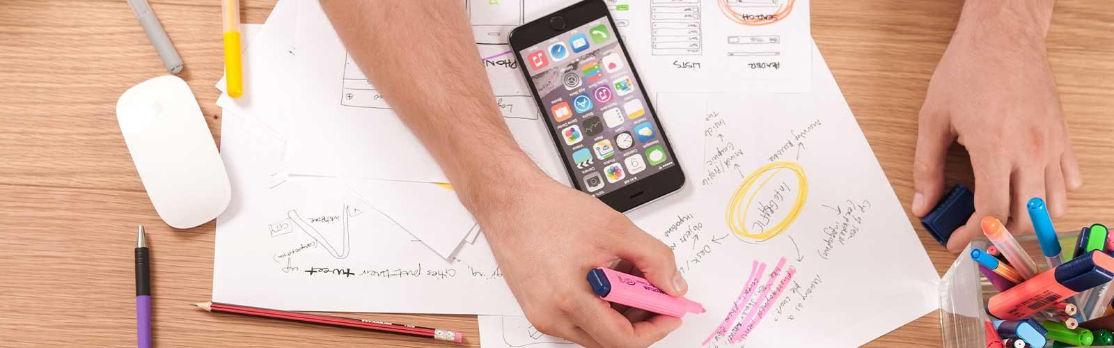 Hand med penna och mobil