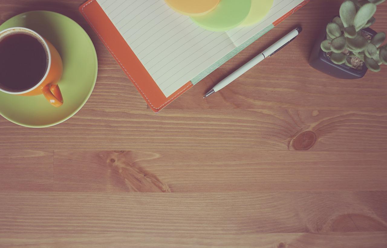 en kaffekopp, enteckningsblock och en krukväxt på träbakgrund
