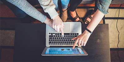 Händer som pekar på en datorskärm