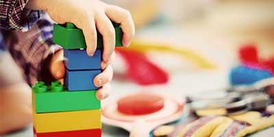 Händer som bygger ett torn i lego